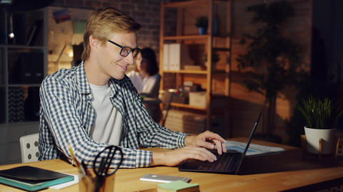 Joyful person working in dark office using laptop late at night smiling Live Action