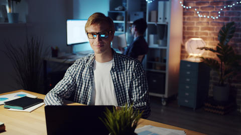 Slow motion of man in glasses looking at camera and smiling in office in evening Footage