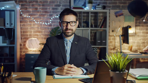 Slow motion portrait of handsome guy office worker smiling in dark workplace Live Action