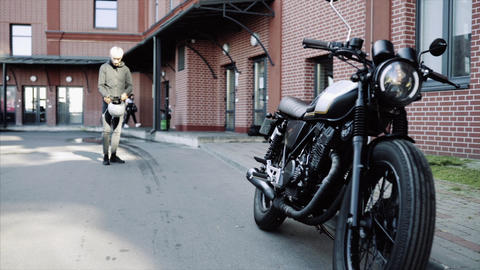 Biker put on helmet, stay behinde motorcycle near office, slow motion Live Action