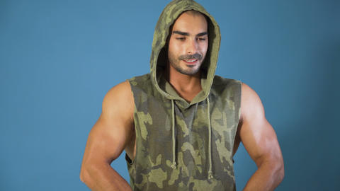 Bodybuilder in camouflage hoodie flexing biceps muscles and chests, studio shot Live Action