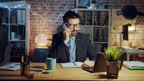 Cheerful guy chatting on mobile phone in office in the evening discussing work Footage