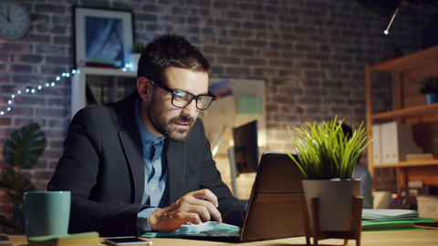 Specialist young man using laptop in dark office smiling feeling happy at work Live Action