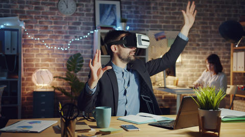 Joyful man using virtual reality glasses at work moving arms in dark office Footage