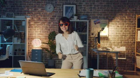Female office worker wearing funny glasses having fun in office in the evening Footage