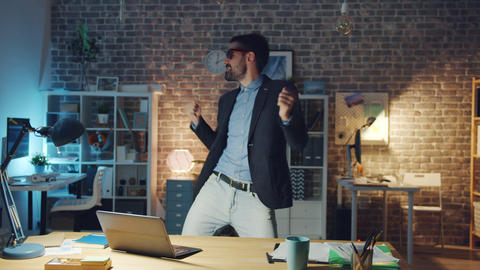Handsome office worker in stylish glasses dancing in office room at night Live Action