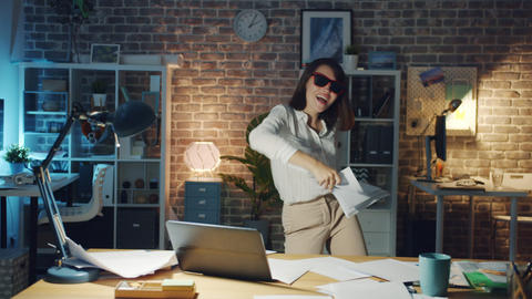 Cheerful manager dancing in office in the evening throwing documents having fun Footage