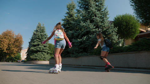 Young active teen girls roller skating outdoor Footage