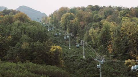 Cable car lifts tourists in luxury mountain resort in summer. Wide-shot of cable Live Action