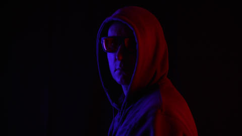Man in sunglasses and hoodie looking at camera in darkness Archivo