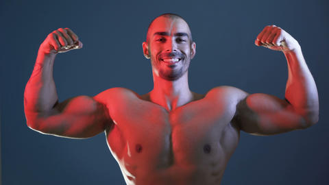 Positive sporty man showing muscular body, flexing arms, chest and shoulders Footage