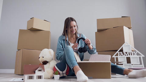 Cheerful likable 30-aged girl having fun alone while unpacking box after Footage
