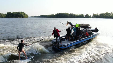 People are filming their wake surfing trip on the river, aerial footage Live Action