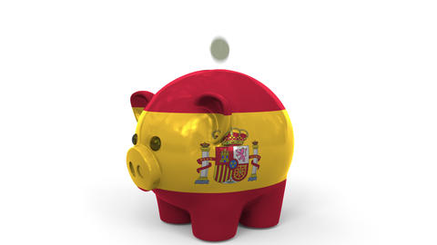 Coins fall into piggy bank painted with flag of Spain. National banking system Live Action