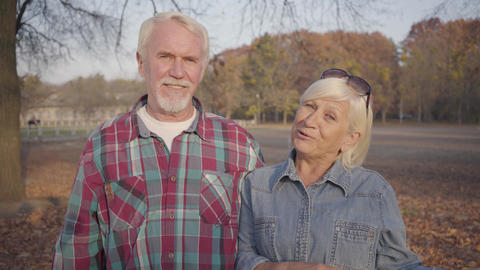 Elderly Caucasian husband and wife standing in sunlight in the autumn park and Footage