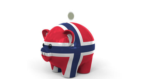 Coins fall into piggy bank painted with flag of Norway. National banking system Live Action