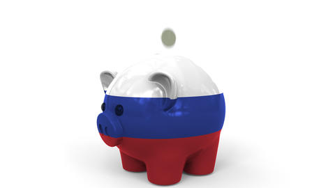 Coins fall into piggy bank painted with flag of Russia. National banking system Live Action