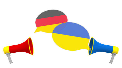 Flags of Ukraine and Germany on speech balloons from megaphones. Intercultural Live Action
