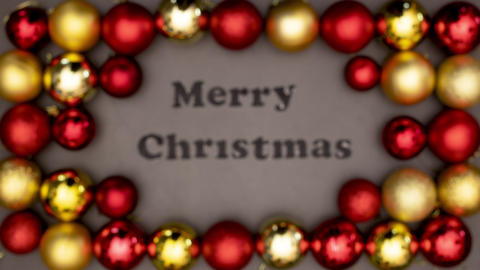 Focusing beautiful frame of gold ad red Christmas balls and Merry Christmas title inside Animation