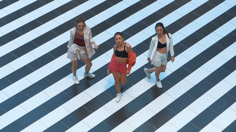 Glamor girls dancing on a striped background top view. Girl dressed in stylish Live Action