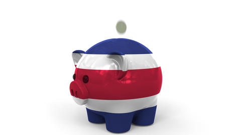 Coins fall into piggy bank painted with flag of Costa Rica. National banking Live Action