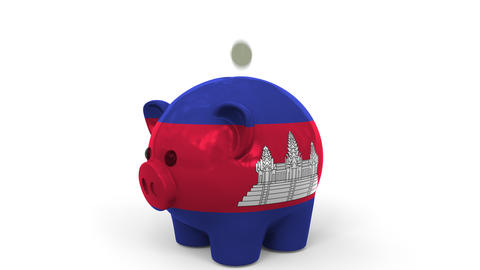 Coins fall into piggy bank painted with flag of Cambodia. National banking Live Action