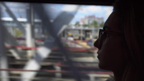 Young woman in glasses is traveling by train. The girl looks out the window Footage