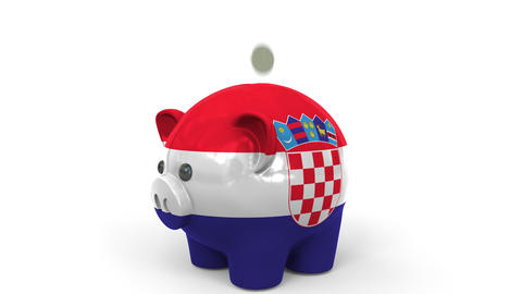 Coins fall into piggy bank painted with flag of Croatia. National banking system Live Action