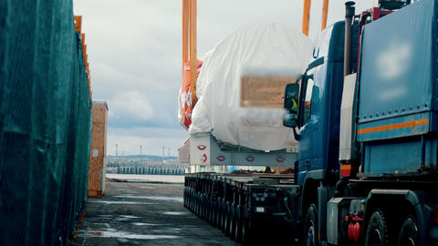 Cargo shipping - a big truck approaches under the cargo and ready for shipment Live Action
