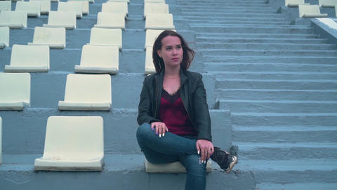 Beautiful and passionate girl in a biker jacket alone sits in an empty stadium Live Action