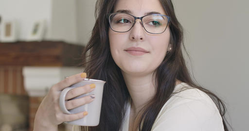 Close-up face of a young thoughtful Caucasian girl in elegant eyeglasses sitting Footage