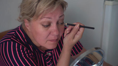 Close up of woman face doing eye makeup with pencil. Adult woman applying pencil Footage