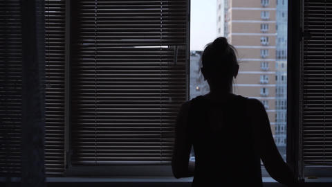 Young adult woman against a window closing a window with shutters. The girl Live Action