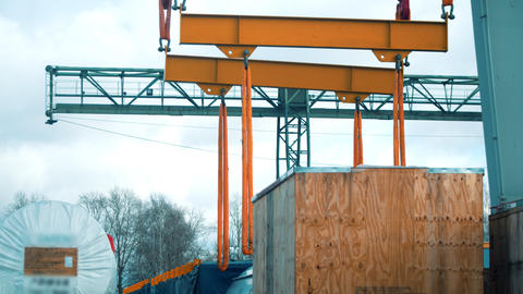 Cargo shipping - a big cargo lifting machine about to lift a big wooden box Live Action