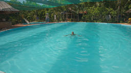 Man Swims in Round Hotel Swimming Pool with Umbrellas Footage