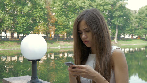 Attractive girl using mobile phone in a city Footage