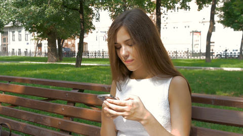 Attractive girl using mobile phone in a city ビデオ