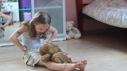 Young girl and brown teddy bear. Girl throws a teddy bear on the floor Footage