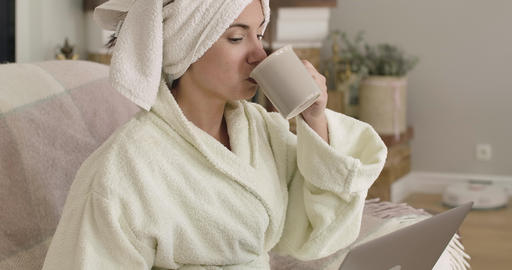 Young thoughtful Caucasian lady in bathrobe and hair towel sitting with laptop Footage