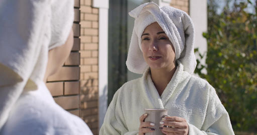 Portrait of young lady in bathrobe and hair towel standing outdoors and, looking Footage
