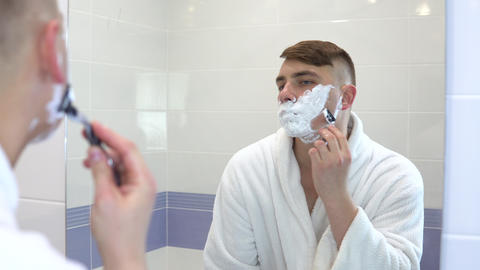 A young man shaves his face hair in front of a mirror. A man in a white coat Footage
