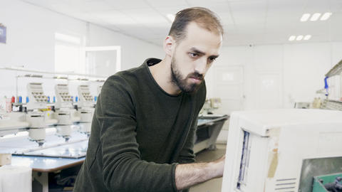 Man working on computer of sewing machine Live Action