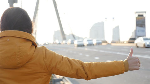 Beautiful girl stops the car. Thumb up. The movement of cars on the road. Hitch Footage