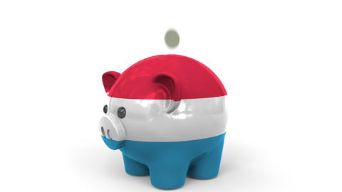 Coins fall into piggy bank painted with flag of Luxembourg. National banking Live Action