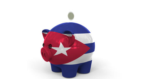 Coins fall into piggy bank painted with flag of Cuba. National banking system or Live Action