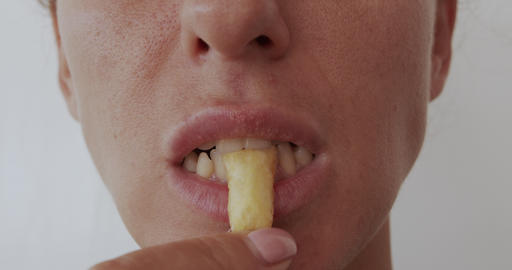 Woman eating French fries, harmful and tasty fast food, close up Footage
