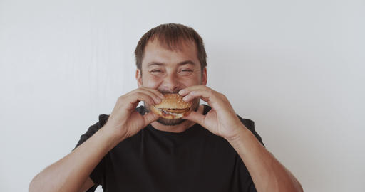 Happy man eating tasty fast food burger Footage