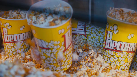 man fills bucket with popcorn in fast food cafe close view Footage