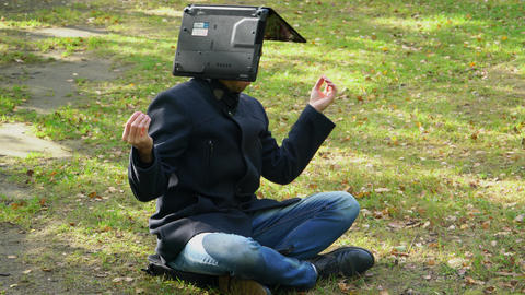 A business man sits in a coat in a Lotus position with a laptop on his head Footage