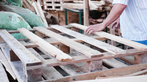 Male worker in a timber factory with a nail gun making a wooden pallet Live Action